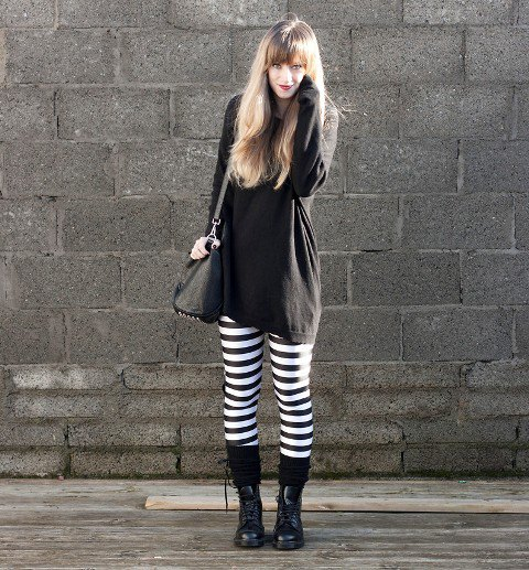 black tunic sweatshirt with striped leggings and boots in the middle of the calf