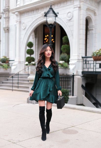black V-neck blouse with ruffles, matching skater skirt and flat over the knee boots