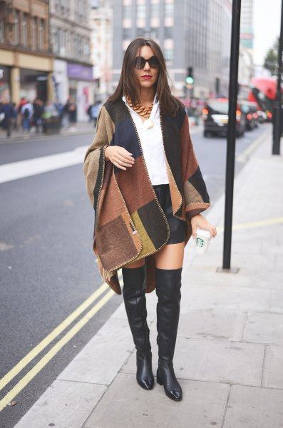 Camel and black black wool coat with flat leather boots over the knee