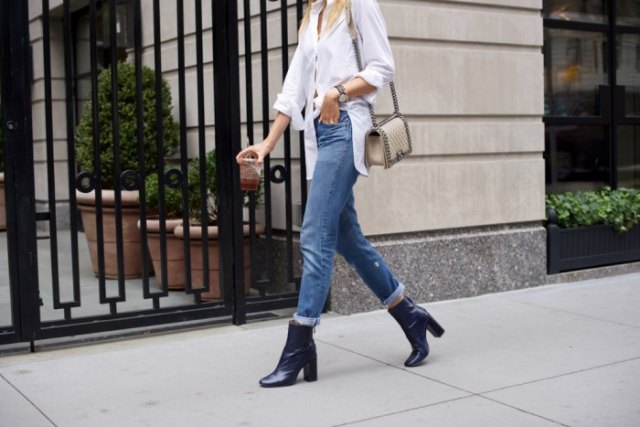white blouse with buttons, jeans with cuffs and dark blue ankle boots with heels