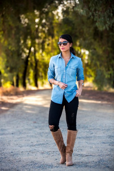 Light blue chambray shirt with buttons, black jeans and flat, knee high boots made of gray suede