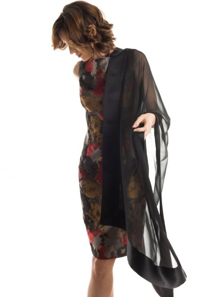 black chiffon cape with a dark, form-fitting midi dress with a floral pattern