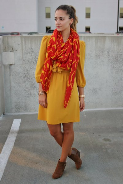 yellow, form-fitting mini dress with orange and gold scarf