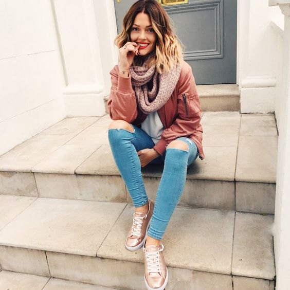 blushing pink bomber jacket with light blue skinny jeans and gold sneakers