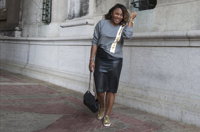 gray sweater with black midi skirt and gold sneakers