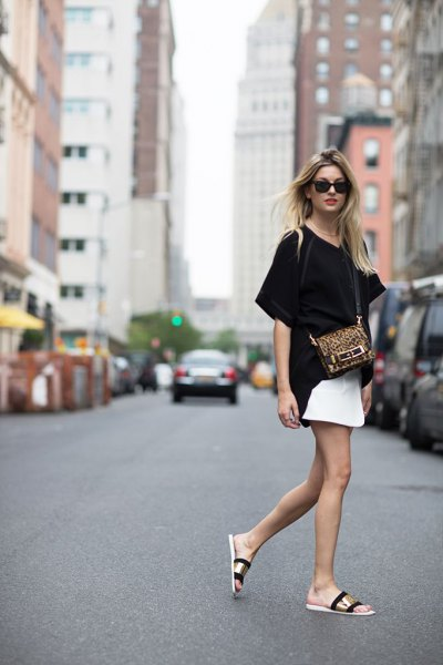 black oversized t-shirt with white mini skirt and gold slippers