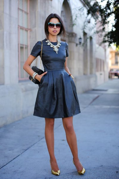 Mini dress made of black and flared leather with gold, pointed evening shoes