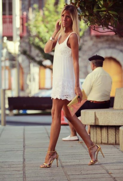 white mini dress with scalloped hem and gold heels with open toes