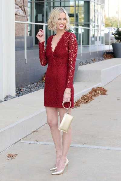 Long-sleeved mini dress made of red lace with a gold clutch