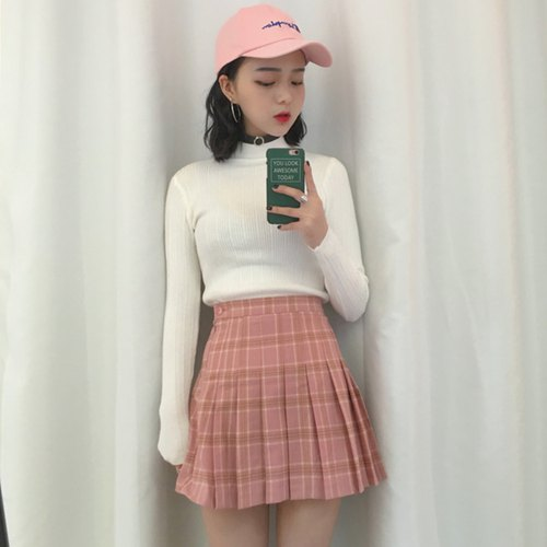 white mock neck sweater with pink, high waisted, pleated mini skirt