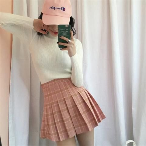 white figure-hugging sweater with pink checkered skirt and white baseball cap