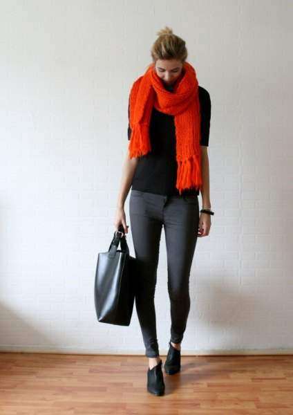 black sweater with orange fringed scarf and gray skinny jeans