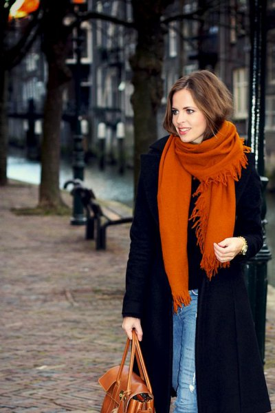 black long wool coat with blue skinny jeans and orange knitted scarf