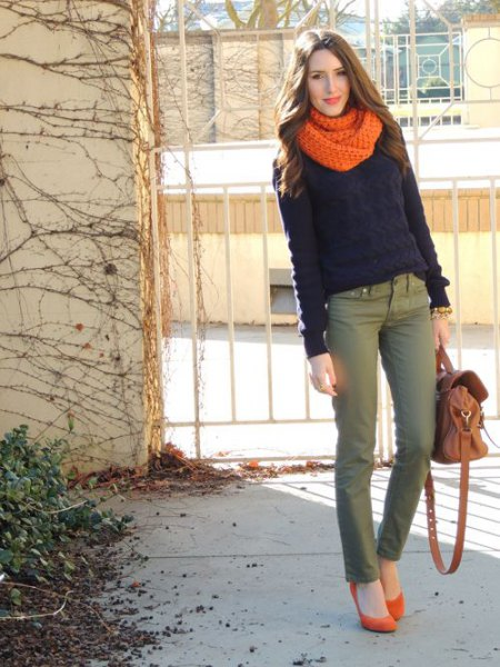 black sweater with orange knitted scarf and gray chinos
