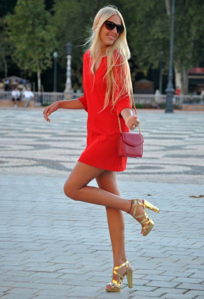 Orange long-sleeved mini dress with a pink small shoulder bag