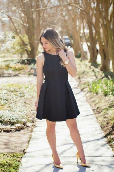 black sleeveless, form-fitting mini dress with golden high heels