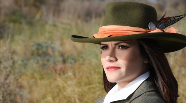 green bush hat with tweed jacket and white collar shirt