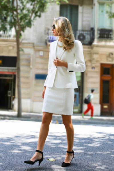 white skirt suit with black, pointed suede ankle strap heels