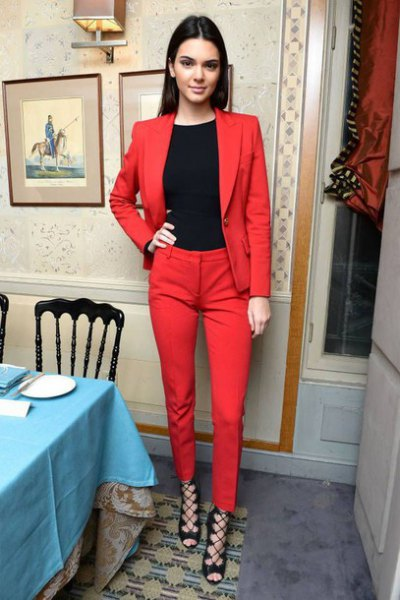 black crew-neck t-shirt, red suit and strappy heels with open toes