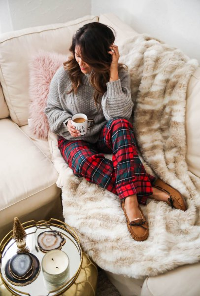 gray cable knit sweater with red and blue checkered pajama bottoms