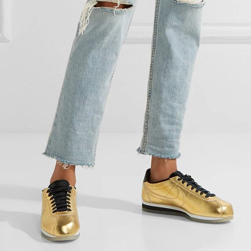 Light blue, torn tubular trousers with golden, comfortable hiking shoes