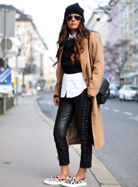 Camel longline wool coat with black leather leggings and canvas shoes with animal motif