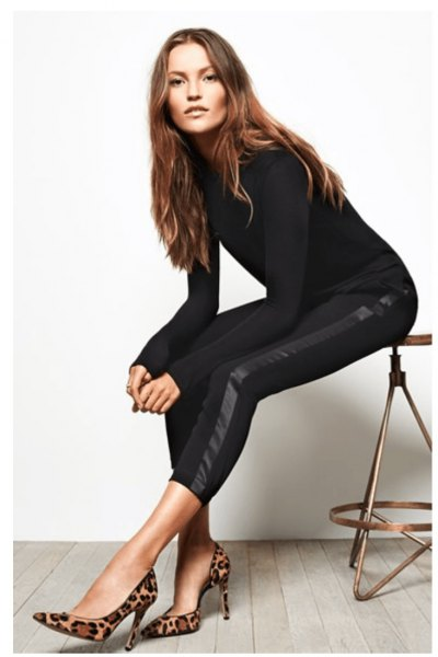 black, figure-hugging long-sleeved sweater with shorts and snake-printed heels
