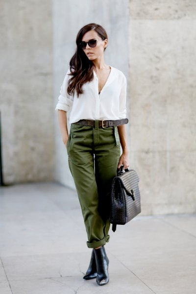 white chiffon blouse with button closure, trousers with green belt and leather chelsea boots