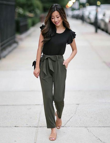 black t-shirt with ruffled sleeves and slim-cut trousers with an army green tie at the front