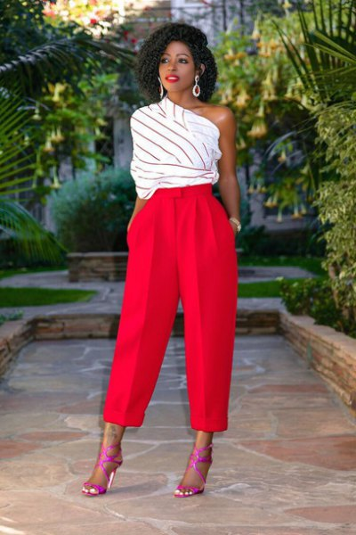 white and gray striped top with one shoulder and red trousers with wide legs