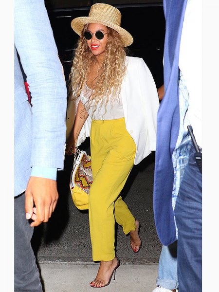 white blazer with mustard yellow trousers with straight legs and straw hat