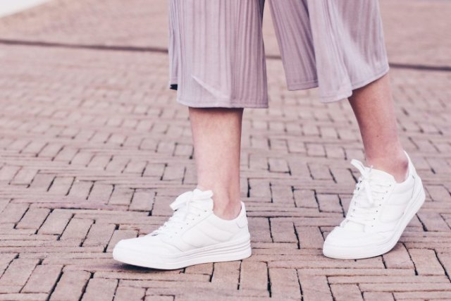 gray striped chiffon trousers with wide legs and white sneakers