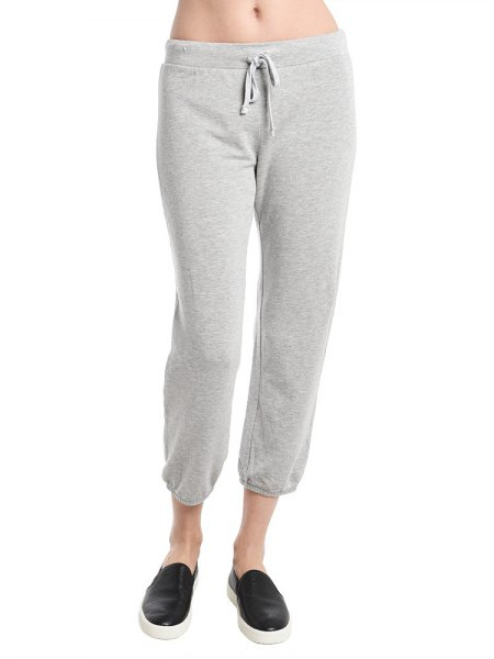 white crop top with light gray fleece pants and low trainers