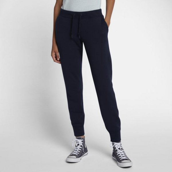 white t-shirt with black fleece pants with conical legs and high trainers
