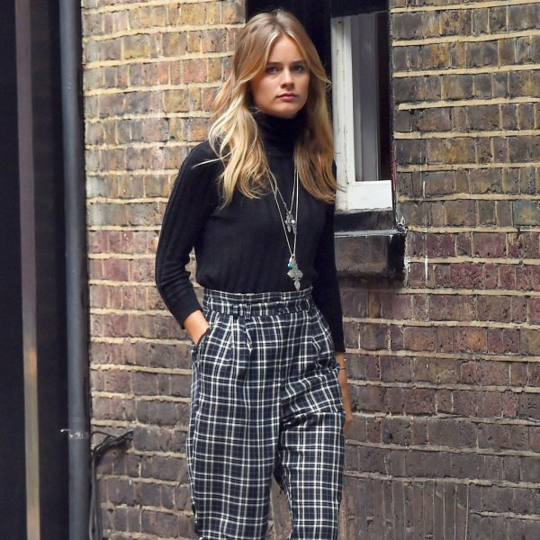 black mock-neck sweater with checked trousers with straight legs