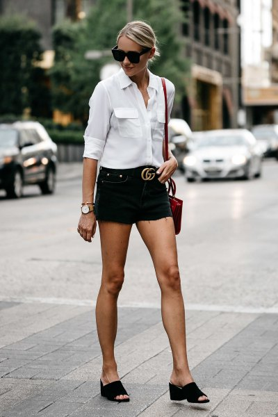 white shirt with buttons and black denim shorts with belt