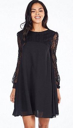 black long-sleeved chiffon mini dress with light pink heels