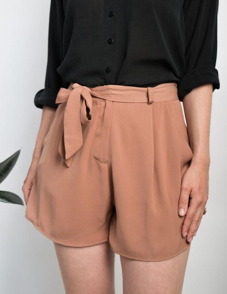 black shirt with cufflinks and blushing pink mini shorts