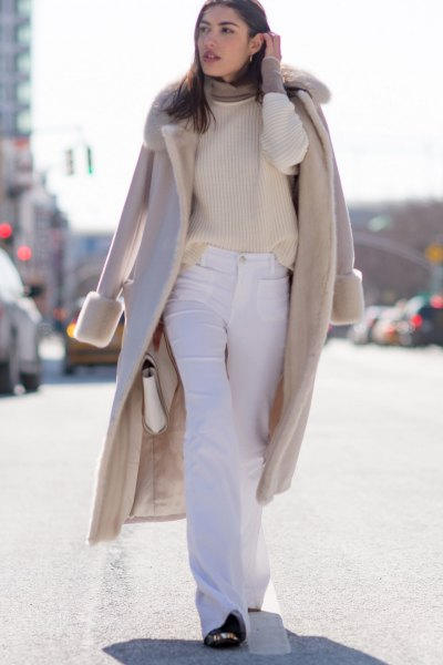 Blushing pink wool coat with faux fur collar and flared white jeans