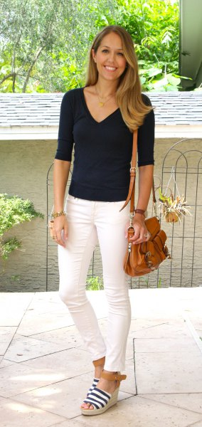 black t-shirt with half sleeve and V-neck and cream-colored ankle jeans