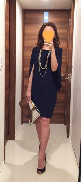 black mini dress with open toe heels and silver metallic clutch handbag