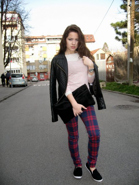 Leather jacket with dark blue and red checked pants and black clutch