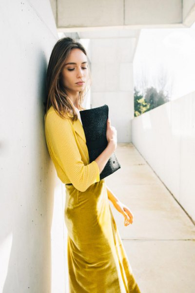 yellow rib sweater with mustard midi dress and black leather clutch
