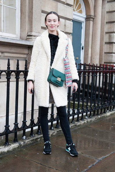 white fleece coat with black leather over the shoulder bag