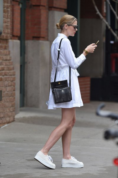 white, long-sleeved shirt dress with fit and flap and black handbag over the shoulder