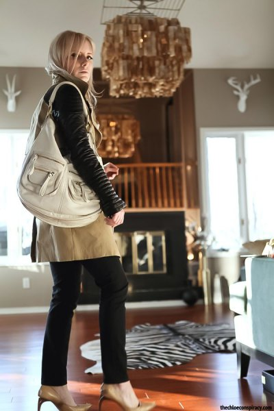 black moto jacket with brown leather skirt and light pink shoulder bag