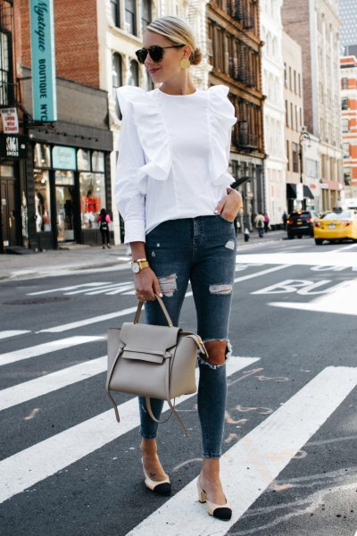 white ruffle shoulder blouse with torn gray skinny jeans