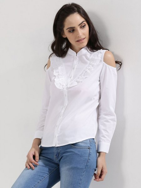 white shirt with ruffles in front and light blue skinny jeans