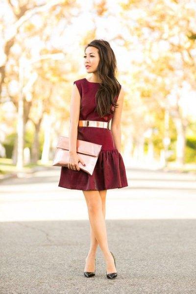 black mini skater dress with belt and rose gold metallic clutch