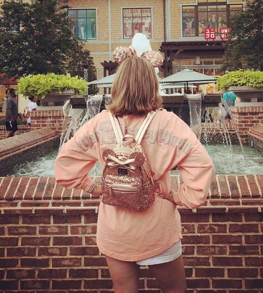 pink oversized long sleeve t-shirt with mini shorts and rose gold backpack wallet